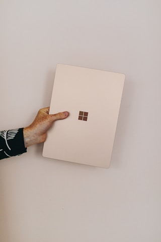 person holding sandstone microsoft Surface laptop laptop